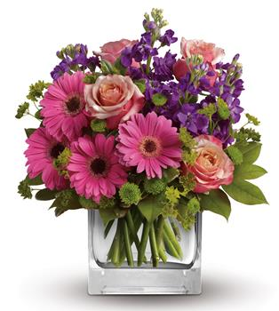 Description: Like the dawn of a fine spring day, this pretty pink gift of gerberas, roses and delicate blue delphinium promises happiness!