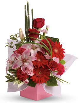 Description: The art of love. Take their breath away with this uniquely sculptural arrangement of lilies, gerberas and canes of bamboo-like equisetum.