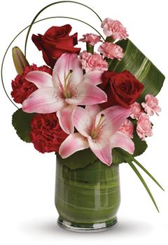 Description: This gorgeous arrangement delivers the spirit of adventure. It is a unique mix of red roses, pink lilies, leaves and lily grass arranged in a chic leaf lined vase.