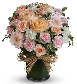Description: Indeed she is! Show her with this soft symphony of feminine blooms, including roses, gerberas and carnations in a raffia lined vase.
