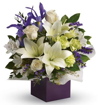 Description: Gorgeous white lilies and delicate blue iris dance gracefully with roses and alstroemeria in this luxurious arrangement.