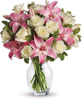 Description: A romantic gift like this one is always appreciated. An eye catching display of roses and lilies is perfectly arranged in a clear vase which makes a beautiful and lasting impression.