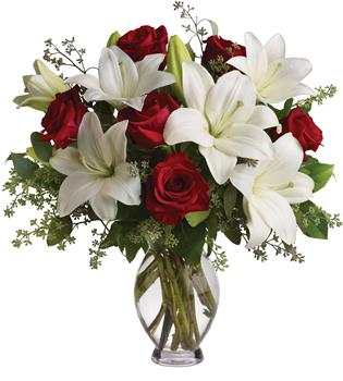 Description: Put these words into flowers with this magnificent arrangement of red roses and white lilies accented with fresh greenery delivered in a classic clear glass vase.