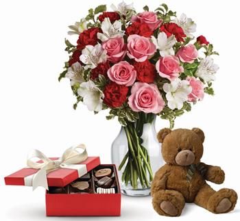 Description: Send this beautiful gift set including a delicious box of chocolates and delightful bear paired with a vase arrangement of light red and pink blooms.