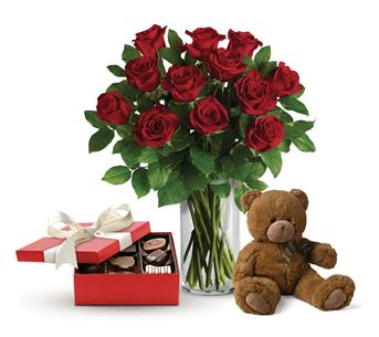 Description: This lavish gift set includes a gorgeous vase arrangement of twelve long stem red roses, accented with greenery, plus chocolates and a delightful bear.