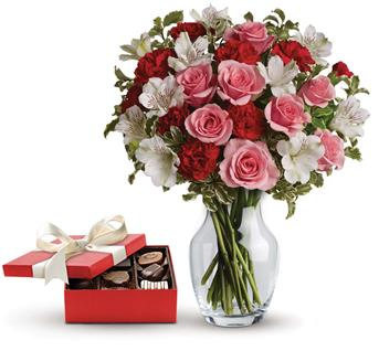 Description: This charming gift set includes a delicious box of chocolates paired with a vase arrangement of light pink spray roses, red miniature carnations and white alstroemeria accented with assorted greenery.