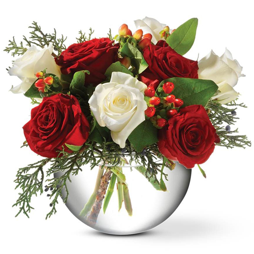Description: A mix of lush ruby and pure white roses, mingled with glossy red berries and greenery, create a classic Christmas arrangement.